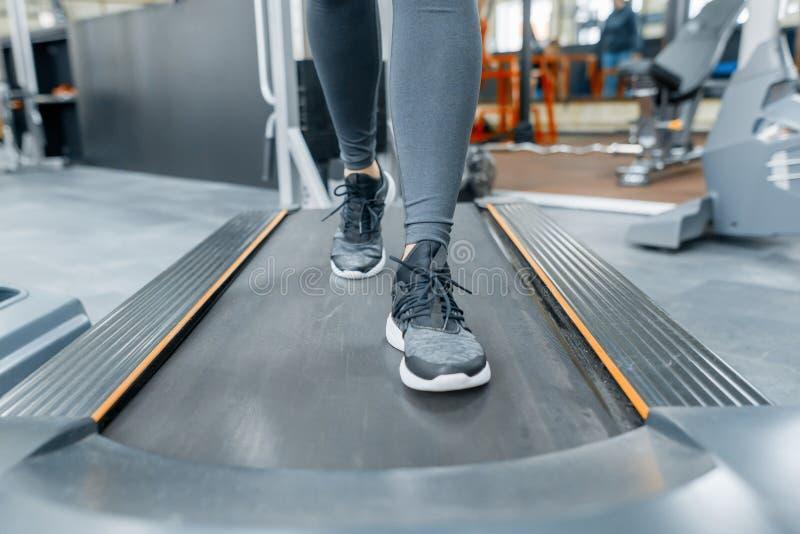 Zbliżenie kobieta cieki biega na karuzeli w gym Sprawność fizyczna, sport, szkolenie, ludzie pojęć fotografia stock