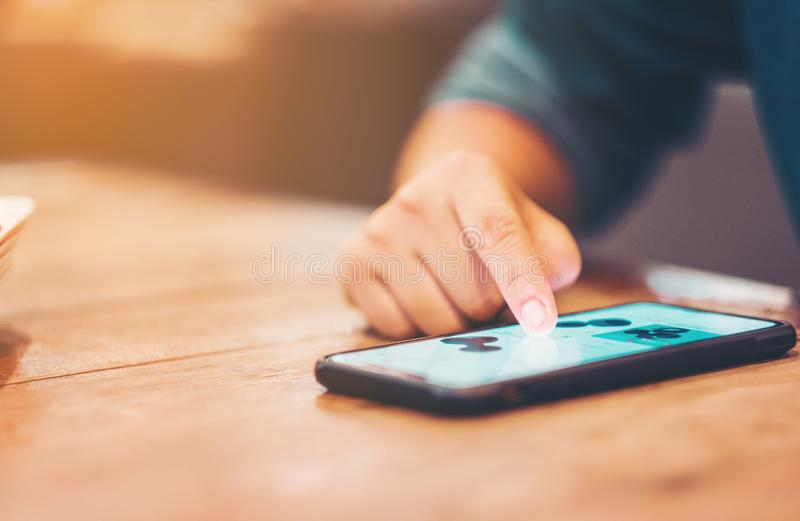 Zbliżenie kobieta używa mobilnego mądrze telefon na z drewnianym tłem fotografia stock