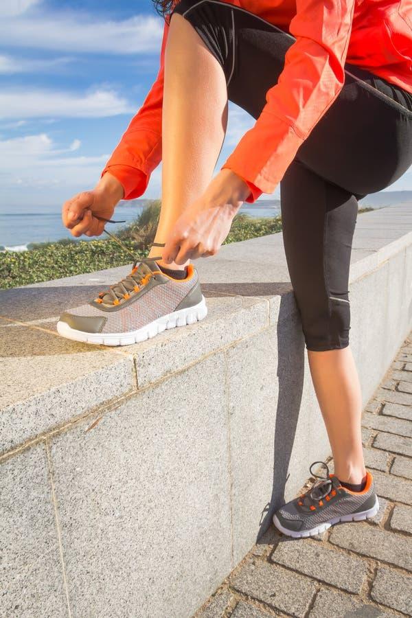 Zbliżenie kobieta wręcza wiązać działających butów koronki obraz royalty free