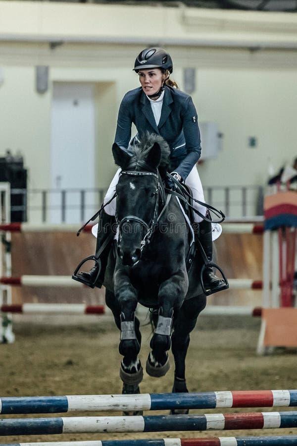Zbliżenie kobiety jeźdza koń pokonuje przeszkoda sportów kompleks indoors obrazy stock