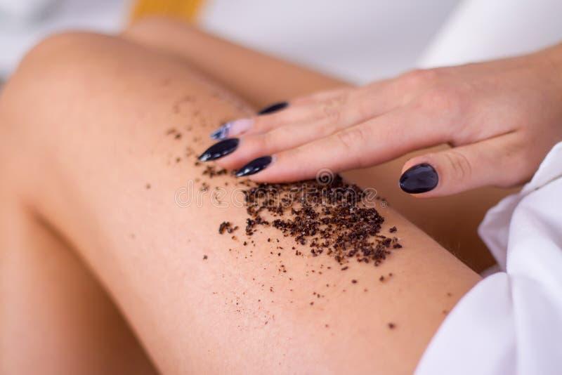 zbliżenie kobiety nogi z kawową masaż pętaczką Kosmetologia, przygotowywać, zdrojów kosmetyczni produkty, piękno i bikini pojęcie fotografia royalty free