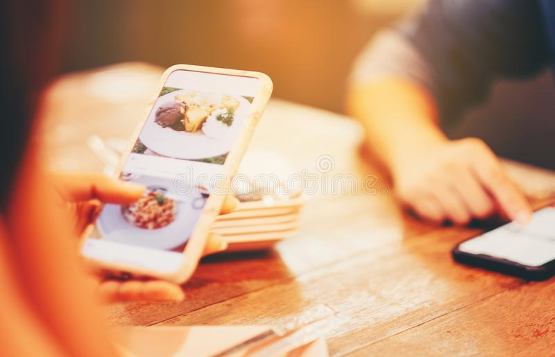 Zbliżenie kobiety ręka używać jego mobilnego mądrze telefon z gmeraniem dla jedzenia na ekranie nad starym drewnianym restauracyj obraz stock
