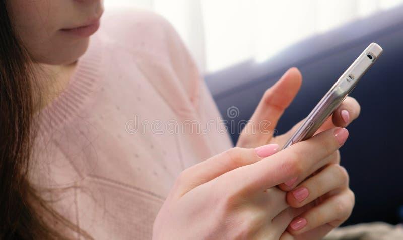 Zbliżenie kobiety ` s wręcza pisać na maszynie wiadomość Unrecognizable kobieta w różowym pulowerze z menchiami robi manikiur zdjęcie stock