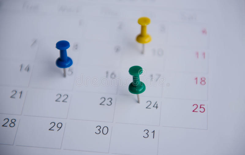 Zbliżenie kolorowe szpilki pchają ocechowanie na kalendarzu napięty plan obraz stock