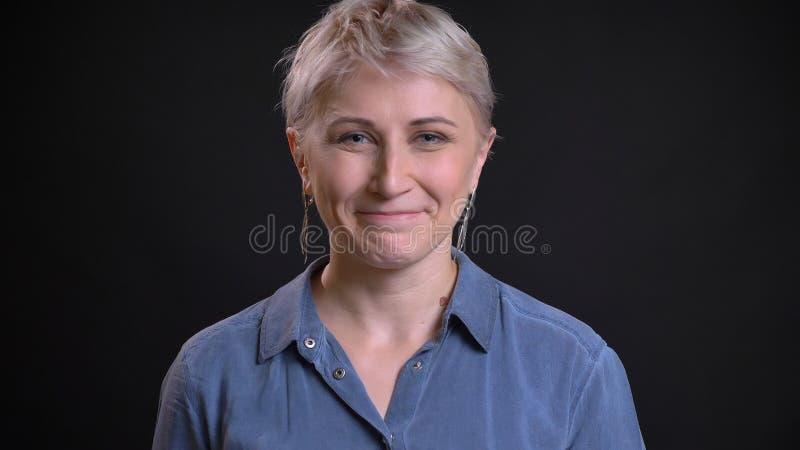 Zbliżenie krótkopęd dorosła atrakcyjna caucasian kobieta jest szczęśliwy, uśmiecha się kamerę z i patrzeje radośnie zdjęcia stock
