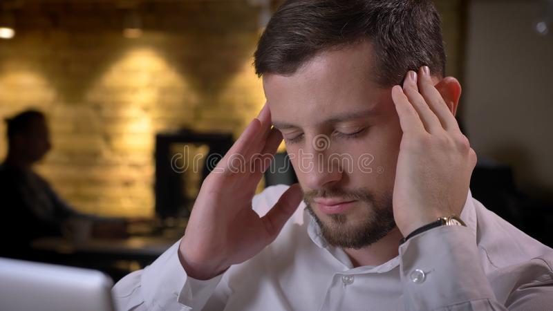 Zbliżenie krótkopęd dorosły caucasian męski pracownik ma migrenę w biurze beind i stresującą się indoors i dewastującą zdjęcia royalty free
