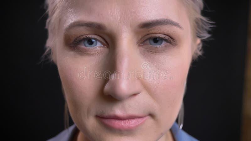Zbliżenie krótkopęd młoda atrakcyjna caucasian kobieta patrzeje prosto przy kamerą z blondynek niebieskimi oczami i włosy obraz stock