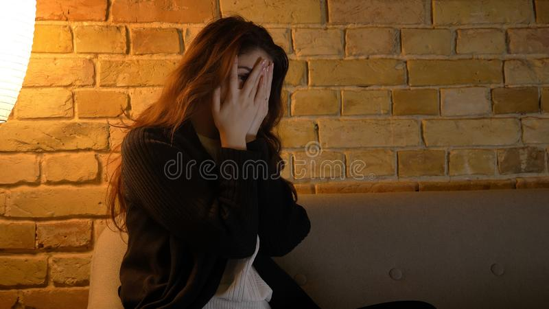 Zbliżenie krótkopęd potomstwo dosyć caucasian kobieta ogląda horror na TV i dostaje straszący podczas gdy siedzący na zdjęcie stock