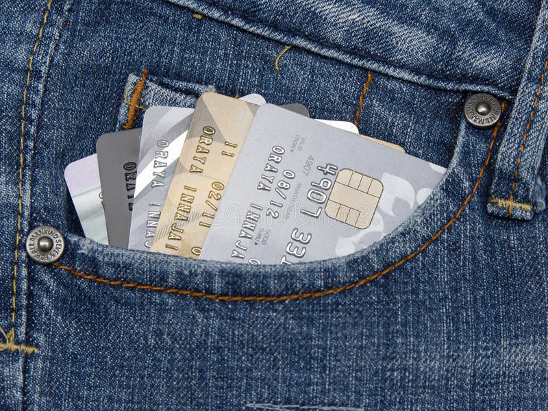 Zbliżenie kredytowa karta w błękitnych drelichowych cajgach wkładać do kieszeni zdjęcia stock