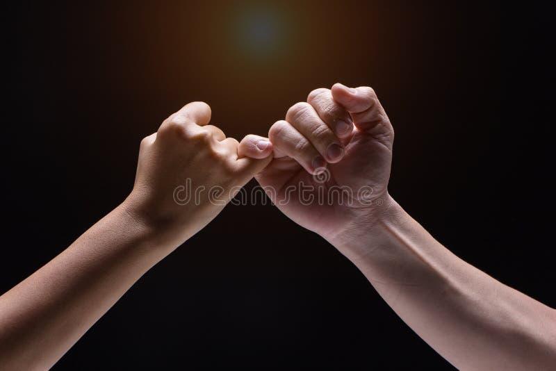 Zbliżenie ludzka ręka, Haczy each innego ` s małego palec na czarnym tle, rozmyty światło wokoło obraz stock
