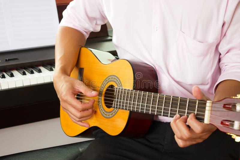Zbliżenie mężczyzna ręki bawić się klasyczną gitarę zdjęcie royalty free