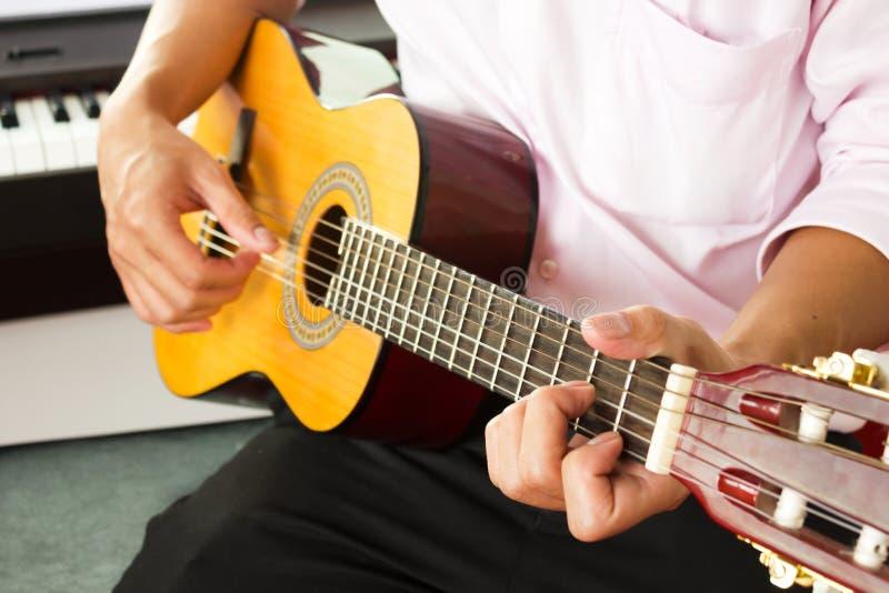 Zbliżenie mężczyzna ręki bawić się klasyczną gitarę zdjęcia stock