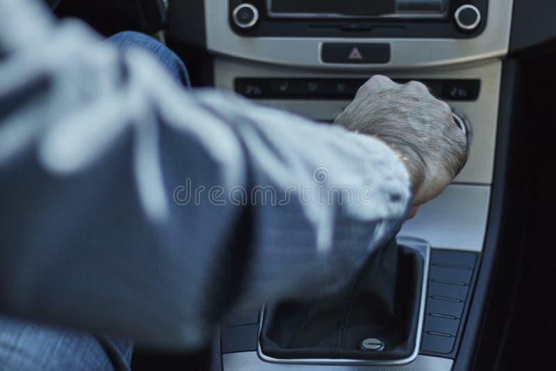 Zbliżenie mężczyzna w samochodowej odmienianie przekładni z jego ręką zdjęcia royalty free