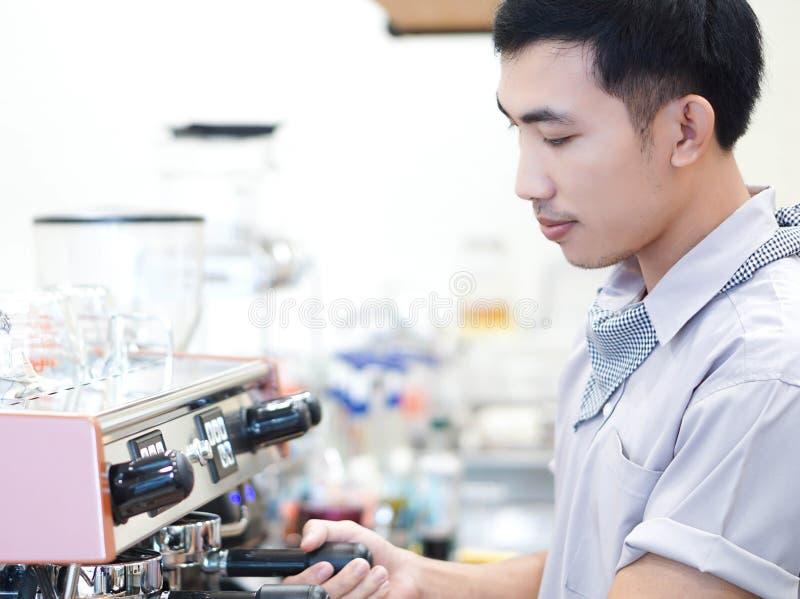 Zbliżenie mężczyzny barista azjatykci narządzanie dla robić kawie przy kawiarnią z szczęśliwym uczuciem obrazy stock