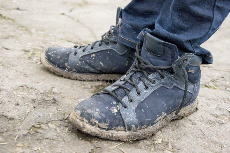 Zbliżenie męscy cieki jest ubranym cajgi i brudzi buty stoi na wiejskiej drodze zdjęcie royalty free