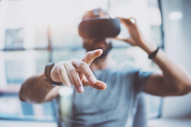 Zbliżenie męska ręka Brodaty młody człowiek jest ubranym rzeczywistość wirtualna gogle w nowożytnym coworking studiu Smartphone u fotografia stock