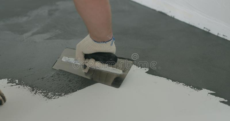 Zbliżenie męski pracownik stosuje mikro betonu tynku narzut na podłoga z kielnią obraz stock