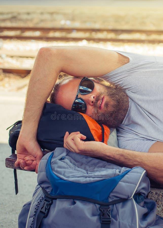 Zbliżenie męskiego backpacker turystyczny drzemanie na ławce obraz royalty free