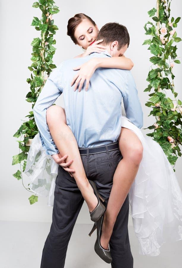 Zbliżenie młoda para w miłości, mężczyzna stojaki z jego plecy kamera, gryźć jego ucho para figlarne ona nogi fotografia stock