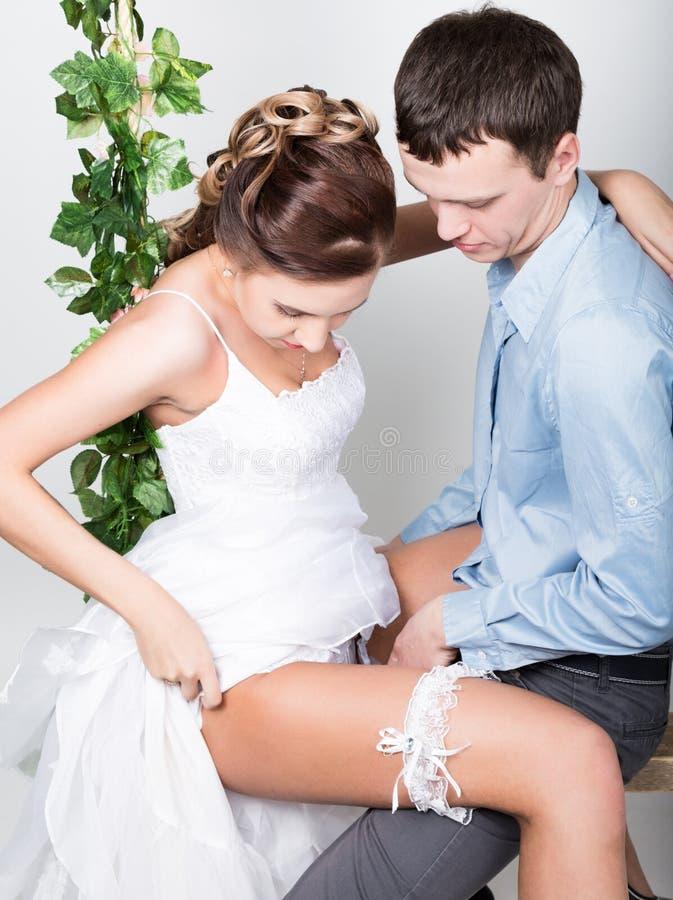 Zbliżenie młoda para w miłości, mężczyzna stojaki z jego plecy kamera, gryźć jego ucho para figlarne ona nogi zdjęcia royalty free