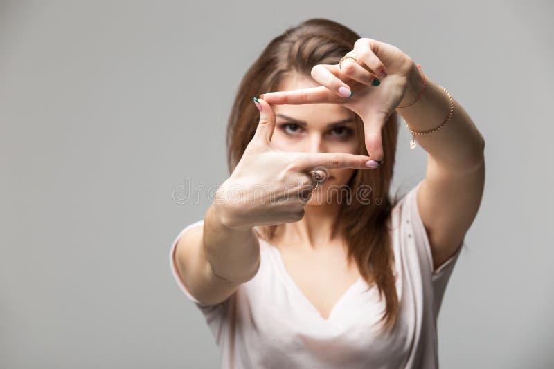 Zbliżenie młoda piękna brunetki kobieta robi ramie z ona palcom, nad szarym tłem obraz royalty free
