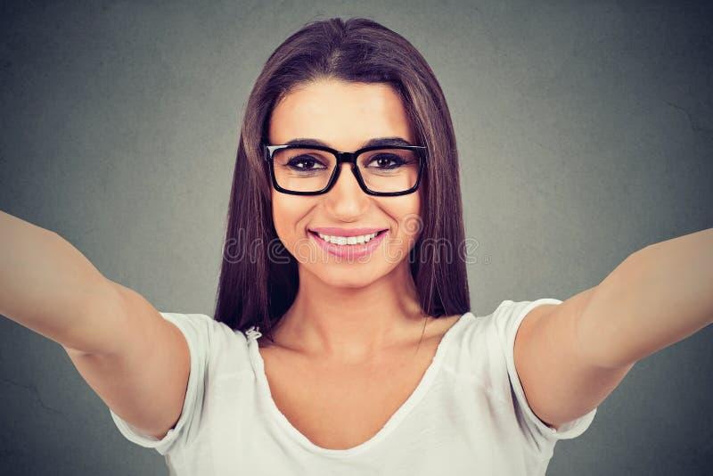 Zbliżenie młoda piękna kobieta w szkłach bierze selfie fotografia stock