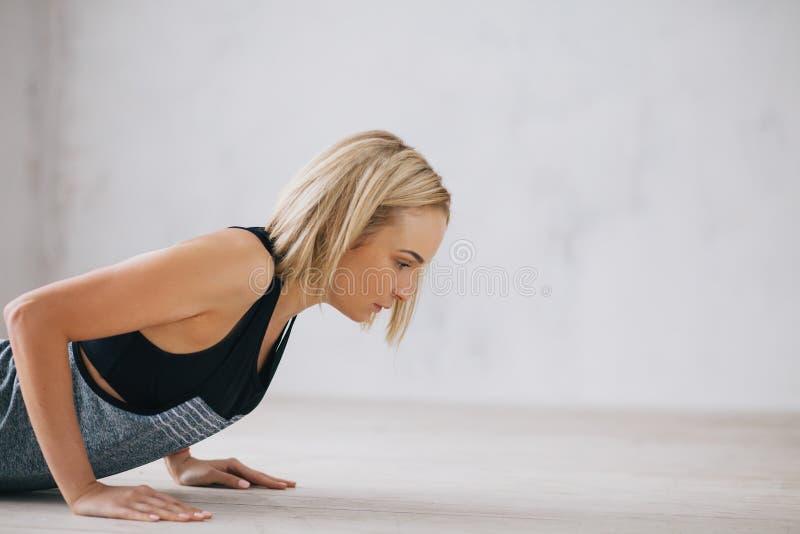 Zbliżenie młoda szczęśliwa atrakcyjna kobieta podnosi robić pcha lub prasa podnosi ćwiczenie obrazy royalty free