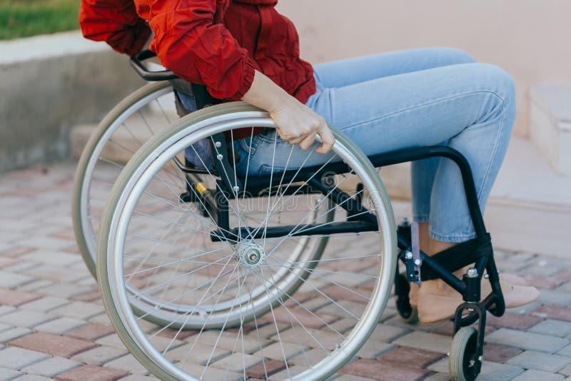 Zbliżenie młodej kobiety na wózku inwalidzkim podczas spaceru w parku w słoneczny dzień Koncepcje naprawy i opieki zdrowotnej obraz stock