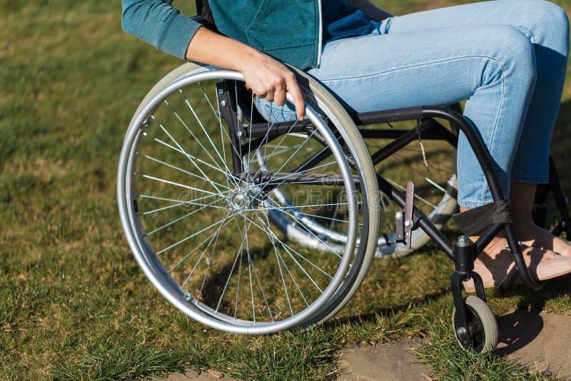 Zbliżenie młodej kobiety na wózku inwalidzkim podczas spaceru w parku w słoneczny dzień Koncepcje naprawy i opieki zdrowotnej zdjęcie royalty free