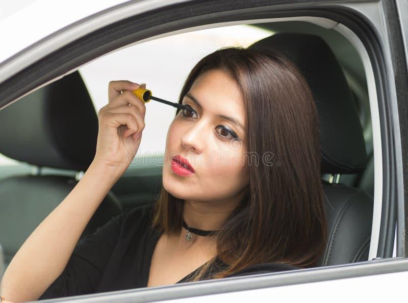 Zbliżenie młodej kobiety obsiadanie w samochodowym kładzeniu na makeup patrzeje w lustrze, jak widzieć od outside kierowców okno, zdjęcie royalty free