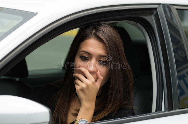 Zbliżenie młodej kobiety obsiadanie w samochodzie oddziała wzajemnie używać języka ciała, jak widzieć od outside kierowcy okno, ż zdjęcia stock