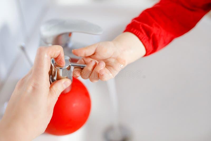 Zbliżenie małe berbeć dziewczyny domycia ręki z mydłem i wodą w łazience Matki lub ojca pomagać blisko do dziecka zdjęcia royalty free