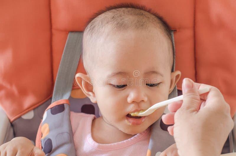 Zbliżenie macierzysta żywieniowa azjatykcia dziewczynka z łyżką w wysokim c obrazy stock