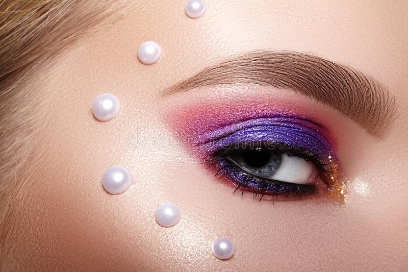 Zbliżenie Makro- kobiety twarz z purpur i menchii oka makijażem Moda Świętuje Makeup, Perls wystrój, Doskonalić kształt brwi zdjęcia stock