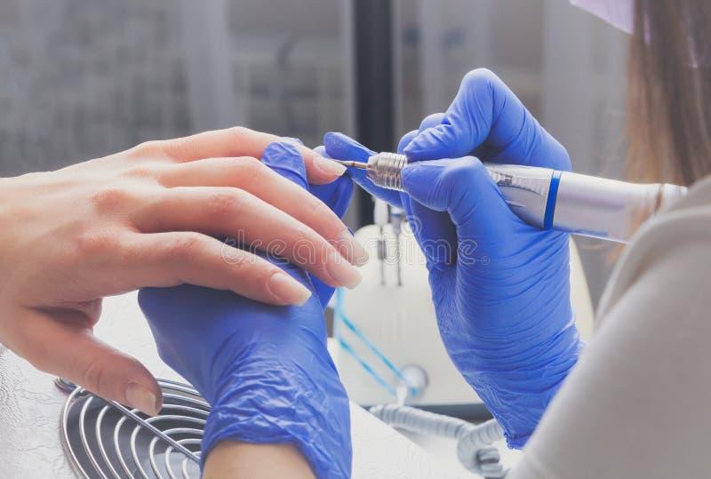 Zbliżenie manicurzysta z mielenie krajaczem dla manicure'u Procedura dla czyścić oskórki na gwoździach fotografia stock