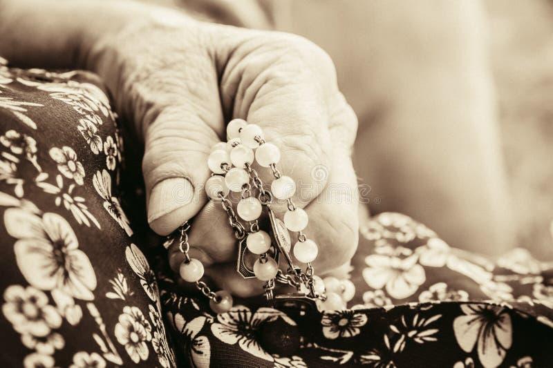 Zbliżenie marszczący stara kobieta wręcza modlenie trzyma chrześcijańskiego różana zdjęcie royalty free