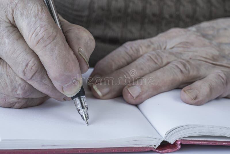 Zbliżenie marszczyć ręki osoby writing zdjęcia stock