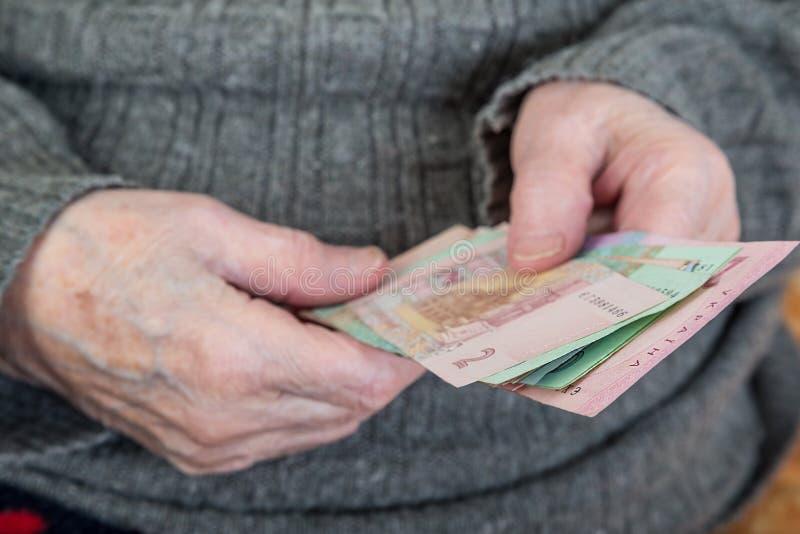 Zbliżenie marszczył ręki starszej osoby odliczający kniaź Hryvnia zdjęcie stock