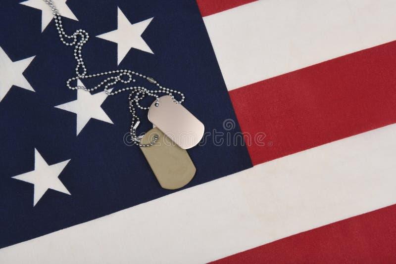 Zbliżenie militarne psie etykietki na fladze amerykańskiej fotografia stock