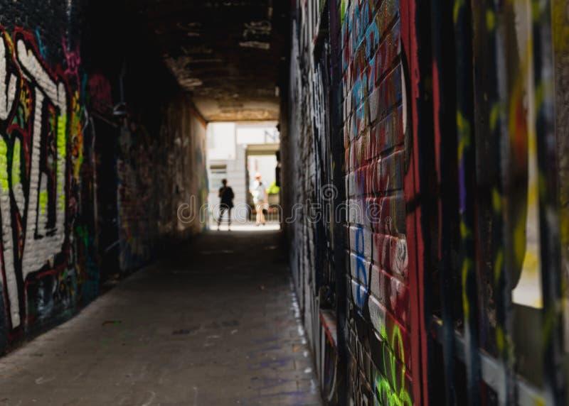Zbliżenie na graffiti ścianie z ludźmi w tle obraz stock