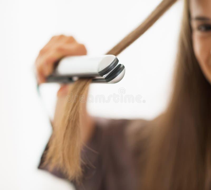 Zbliżenie na kobiecie prostuje włosy z prostownicą obrazy stock