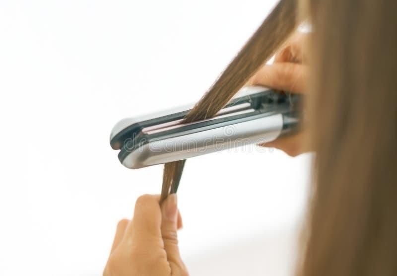 Zbliżenie na kobiecie prostuje włosy z prostownicą Tyły rywalizuje fotografia royalty free