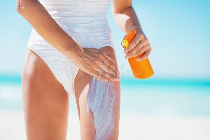 Zbliżenie na młodej kobiecie stosuje słońca blokowego creme na plaży fotografia royalty free