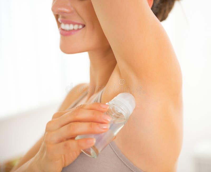Zbliżenie na szczęśliwej młodej kobiecie stosuje dezodorant zdjęcie royalty free