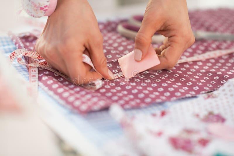Zbliżenie na szwaczce robi ocenom na tkaninie obrazy royalty free