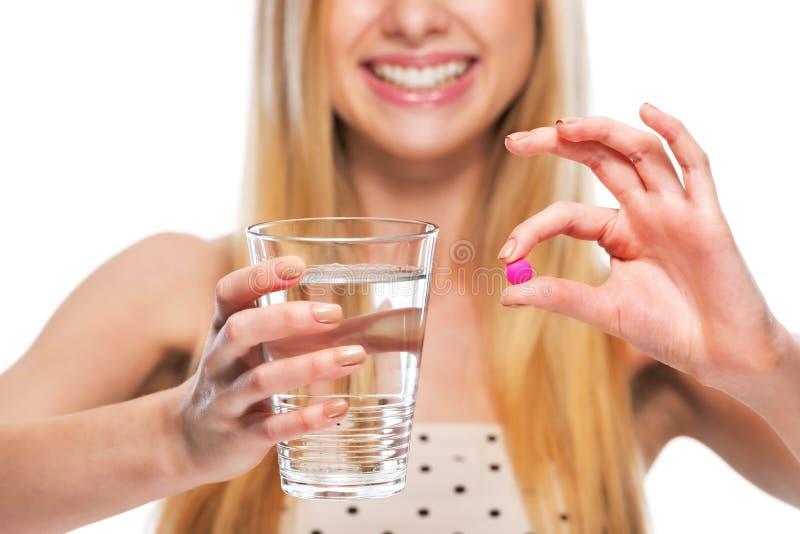 Zbliżenie na uśmiechniętej nastoletniej dziewczynie daje filiżance woda i pigułka zdjęcie stock