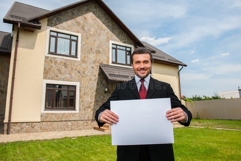 Zbliżenie na uśmiechniętym agencie nieruchomości przygotowywającym sprzedawać dom zdjęcia stock