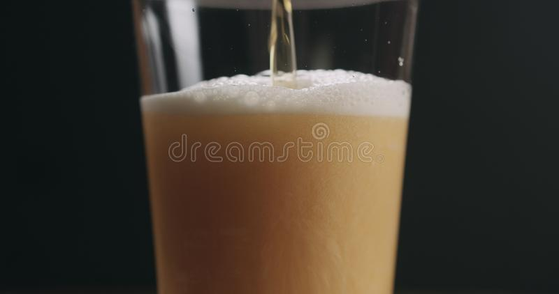 Zbliżenie nalewa lekkiego ale piwo w pół kwarty szkle nad czarnym tłem obraz royalty free