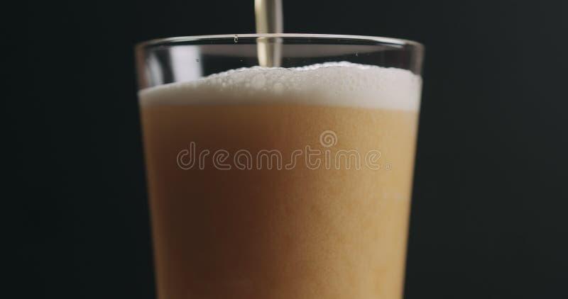 Zbliżenie nalewa lekkiego ale piwo w pół kwarty szkle nad czarnym tłem obraz stock