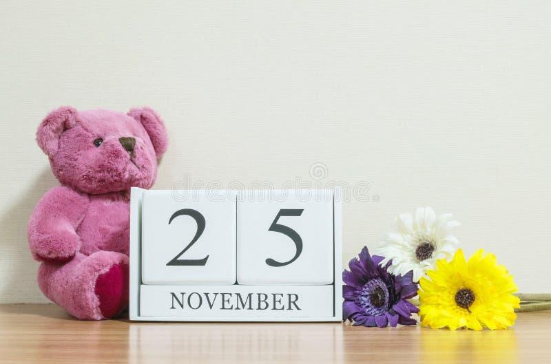 Zbliżenie nawierzchniowy biały drewniany kalendarz z czerń 25 Listopadu słowem na brown drewnianym biurku i kremowej kolor tapeci zdjęcia royalty free